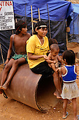 Amazon, Brazil. Young Yanomami woman with her children beside an illegal gold mine airstrip asking for food.