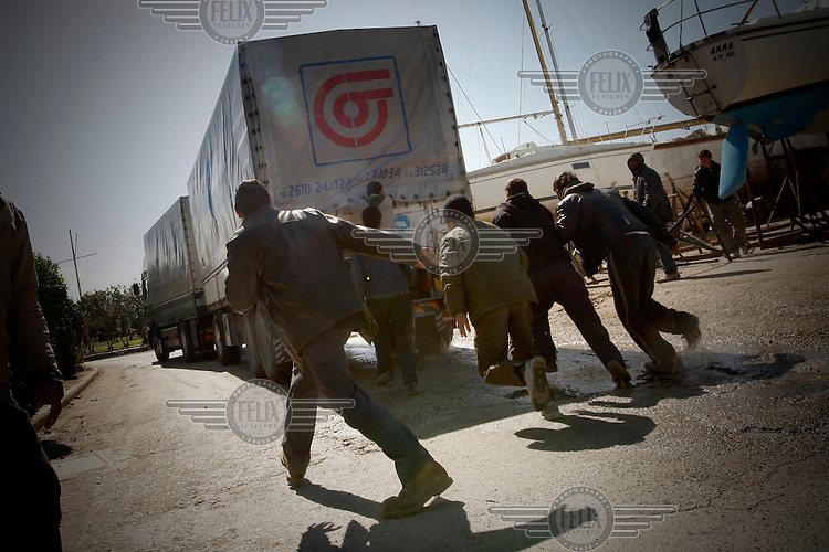 Greece / Patras /March 10,2009. Near the port of Patras, immigrants running after a truck that heads to Italy. The port of Patras is one of the biggest crossing points to continental Europe. Thousands of the immigrants in Greece gather in the country's biggest ports, in hopes of stowing away on one of the trucks loaded onto Italy-bound ships and ferries. Day and night, they sprint after the trucks as they pass through the gates, trying to latch onto the doors or crawl into the wheel wells. During the last years, in their effort to continue their journey, dozens have been found dead died suffocation inside the trucks.  Giorgos Moutafis