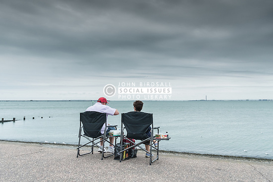 A couple having a picnic on Southend seafront in Essex.