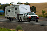 Ford work truck towing travel trailer.