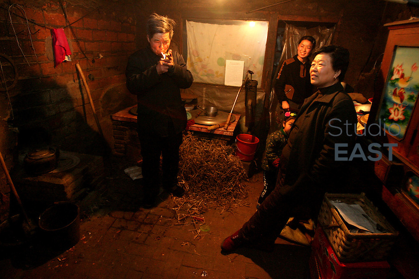 Farmers in the kitchen of a two-room mud house in Yongfu village, on February 27, 2006. Photo by Lucas Schifres/Pictobank