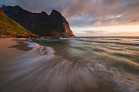 Midnight sun light shines across Kvalvika beach, Moskenesøy, Lofoten Islands, Norway