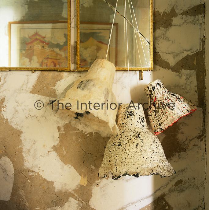 Three decorated, painted lampshades hang from a mirror.