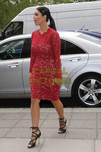 Kim Kardashian arriving at her hotel,.London, England..May 18th, 2012.full length red pink lace dress black strappy sandals side profile ponytail.CAP/HIL.©John Hillcoat/Capital Pictures.