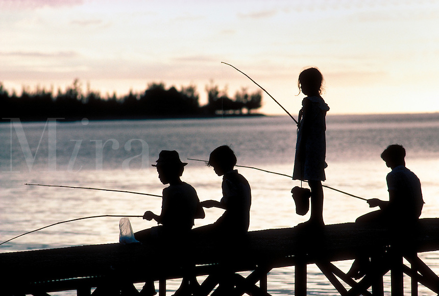 Silhouette of children fishing in the evening Florida sunshine