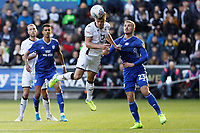 Jake Bidwell of Swansea City (C) heads the ball forward, challenged by Danny Ward of Cardiff City (R) during the Sky Bet Championship match between Swansea City and Cardiff City at the Liberty Stadium, Swansea, Wales, UK. Sunday 27 October 2019