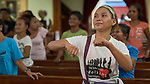 Methche Bayan moves her arms as she sings during worship at Knox United Methodist Church in Manila, Philippines. The service is part of a weekday program where the church opens up to poor people in the neighborhood, offering showers, food, fellowship, and an opportunity to worship together.