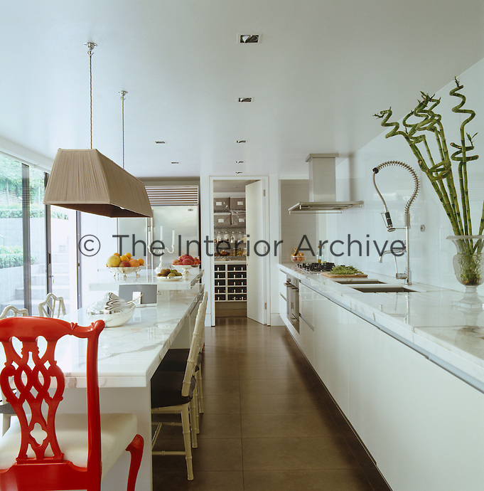 View down the length of the white marble kitchen through the open door into the larder