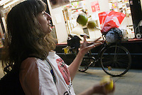 Janet juggles ripe apples that have been recovered from the trash outside D'Agnostino's.