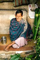 A Hindu man sits cross-legged at his small stall at a street market in Kolkata, India.