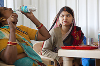 India. Uttar Pradesh state. Allahabad. Maha Kumbh Mela. Two Indian Hindu devotees are seated in a restaurant. One woman drinks Bisleri water from a plastic bottle. Bisleri is a brand of bottled water and has 60% market share in packaged drinking water in India. The Kumbh Mela, believed to be the largest religious gathering is held every 12 years on the banks of the 'Sangam'- the confluence of the holy rivers Ganga, Yamuna and the mythical Saraswati. The belief is that bathing and taking a holy dip will wash and free one from all the past sins, get salvation and paves the way for Moksha (meaning liberation from the cycle of Life, Death and Rebirth). The Maha (great) Kumbh Mela, which comes after 12 Purna Kumbh Mela, or 144 years, is always held at Allahabad. Uttar Pradesh (abbreviated U.P.) is a state located in northern India. 7.02.13 © 2013 Didier Ruef