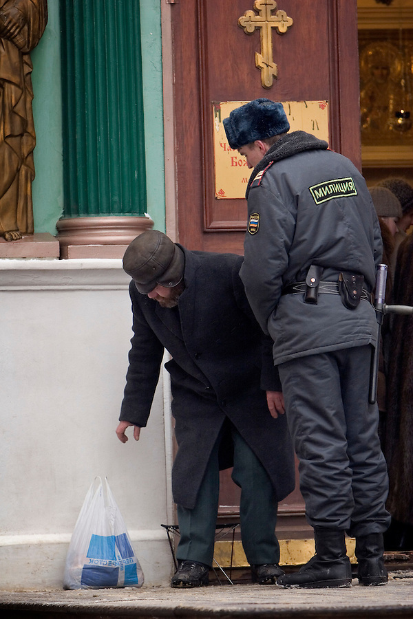 Moscow, Russia, 20/02/2005..A homeless beggar is moved from the entrance to Red Square for a Russian policeman.