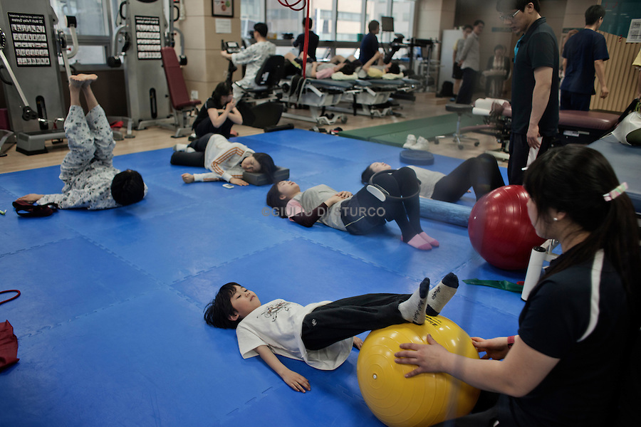 Clinical session of exercises of a seven years old Child in a Western-type growth in Seoul, April 2011.Driven by the belief, increasingly popular, that the height is essential to success, South Korean parents try all kinds of remedies to increase the stature of their children, making use of hundreds of clinics that offer growth hormones, medical traditional treatments, such as acupuncture, and treatments and special exercises.