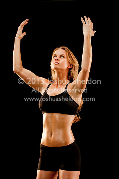 Young muscular woman facing forward, arms raised over head