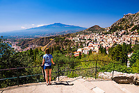 Taormina, tourist looking at Mount Etna Volcano and Taormina Town from Teatro Greco aka Taormina Greek Theatre, Sicily, Italy, Europe. This is a photo of a tourist looking at Mount Etna Volcano and Taormina Town from Teatro Greco aka Taormina Greek Theatre, Sicily, Italy, Europe