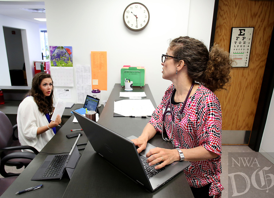NWA Democrat-Gazette/DAVID GOTTSCHALK  Marr-Lynn Flory (right), medical practitioner, speaks with Rachel Best, volunteer, Wednesday, June 21, 2017, at the nurses station at WelcomeHealth in Fayetteville. WelcomeHealth is paying about 12 percent, or $102,000 of its annual budget to University of Arkansas for Medical Sciences. The nonprofit also put about $700,000 of its own money into the old building to provide better community, medical service to low-income 'working poor' people. UAMS is making thousands off of property it doesn't own by subleasing Washington County's property back to businesses and nonprofits.  Now, Washington County officials are researching ways to take back that property, get out of the UAMS lease and get that revenue for itself. The county has already promised one struggling nonprofit a lower rent than what UAMS currently charges.