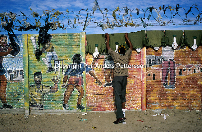 An unidentified man hangs rugby shirts that have been laundered on a colorful wall with graffiti on July 5, 2001 in Site C Khayelitsha, a township about 35 kilometers outside Cape Town, South Africa. The township has about one million people living there. Khayelitsha is one of the poorest and fastest growing townships in South Africa. People usually come from the rural areas in Eastern Cape province to find work as maids and laborers. (Photo by: Per-Anders Pettersson)