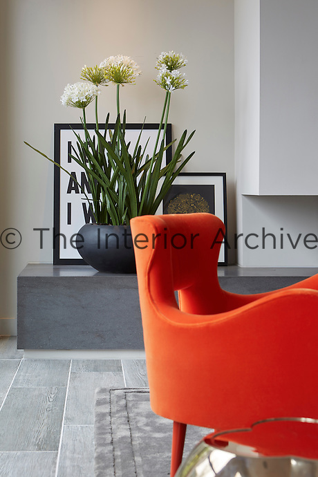 A shaped orange chair stands in front of the slate hearth of the fireplace.
