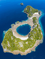 aerial view of a limestone island with a blue hole in Raja Ampat Islands, West Papua, Indonesia, Pacific Ocean