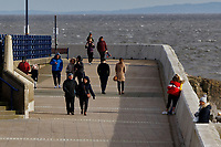 Pictured: People go for a walk, not observing social distancing, at the sea front  in Porthcawl, Wales, UK. <br /> Re: Covid-19 Coronavirus pandemic, UK.