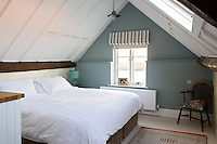 In a cosy attic bedroom the far wall has been painted a subtle sage green offsetting a striped contemporary roman blind and an antique Windsor chair