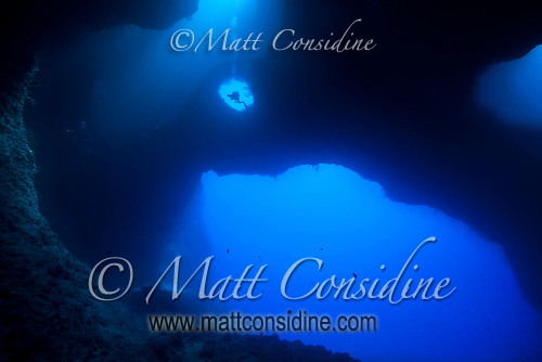 Diver leaving Blue Holes through an eye in the wall of the cave, Palau Micronesia (Photo by Matt Considine - Images of Asia Collection) (Matt Considine)