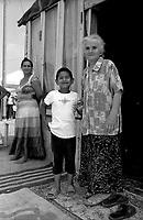 milano, periferia nord. campo di nomadi rom romeni di via triboniano. nonna e nipote e la madre sullo sfondo --- milan, north periphery. rumanian nomads camp of triboniano street. grandmother and grandson and the mother and the background