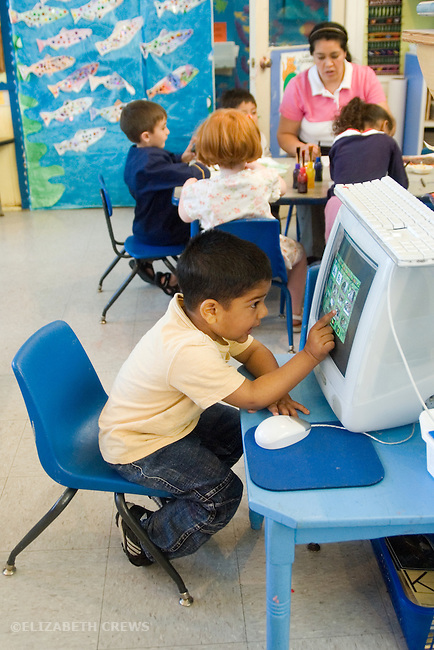 Berkeley CA Four-year-old doing learning game on classroom computer, group doing art in background, at bilingual, Spanish-English preschool