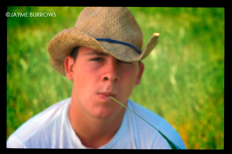 Young man sitting in long grass.