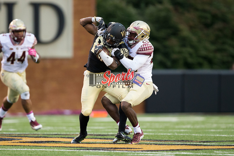 Chuck Wade (89) of the Wake Forest Demon Deacons is tackled by Trey Marshall (20) of the Florida State Seminoles after catching a pass during second half action at BB&T Field on October 3, 2015 in Winston-Salem, North Carolina.  The Seminoles defeated the Demon Deacons 24-16.   (Brian Westerholt/Sports On Film)