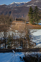 "Switzerland. Canton Ticino. Cureglia is a municipality in the district of Lugano. ""Tiratori del Gaggio"" society. View on the shooting range from the targets distants 300 meters. Snow and trees in winter season. Car on the road. Snowy Alps.  9.02.2019 © 2019 Didier Ruef"