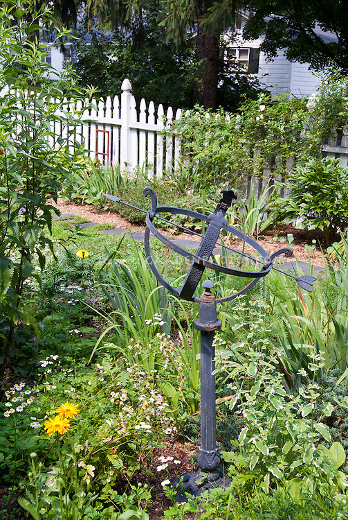 Armillary Sundial in garden with picket fence, house, focal point