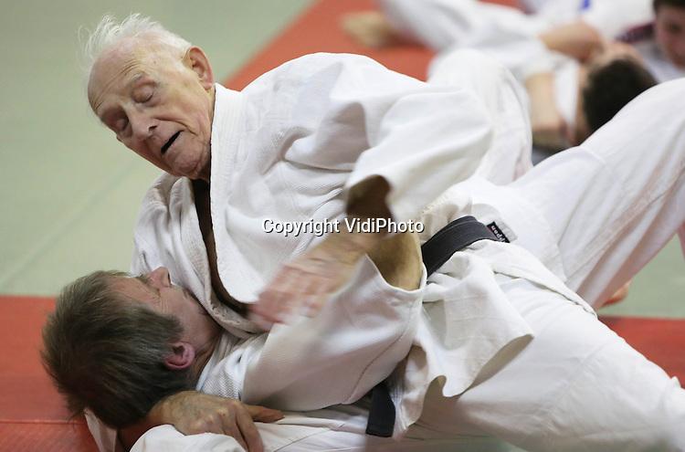 Foto: VidiPhoto..DOESBURG - De 90-jarige Wim van Delden uit Doetinchem traint donderdag in zijn Doesburgse sportschool. Van Delden is met stip de meest fitte hoogbejaarde van Nederland en tevens de enige actieve vechtsporter van die leeftijd. De drager van de zwarte band heeft de tweede dan jiujitsu en zet zijn arm- en beenklemmen nog als een jonge vent, vertelt zijn Sensei. Tweemaal in de week .traint de ninja opa bij Sport- en Recreatie-instituut Doesburg met sporters die tientallen jaren jonger zijn. Alleen zijn conditie blijft wat achter bij de rest. Foto: Wim van Delden met zijn vaste sparringpartner, de 60-jarige Henk van Achterberg uit Beek..