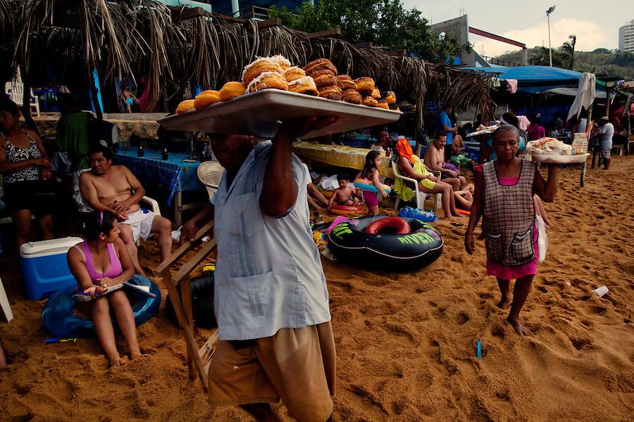 Acapulco, Mexico, February 18, 2012 – Vendors carry doughnuts and ceviche the beach on the Bahia De Puerto Marquez.