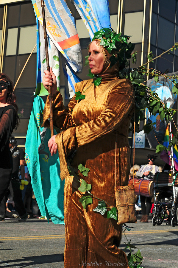 A woman costumed in gold and ivy participates in Olympia, Washington's Procession of the Species.