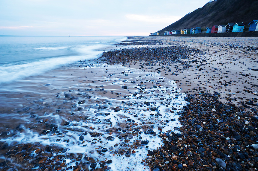 The north sea reaches up onto the shore, with typical Norfolk beach huts at the high tide mark, at Cromer, Norfolk.