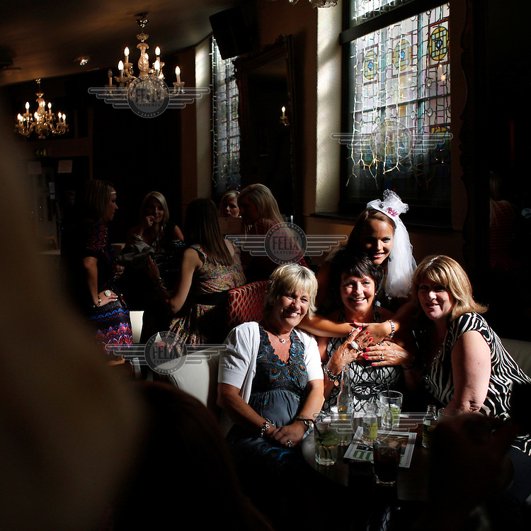 A group of women celebrating a 'hen night', a pre-wedding women-only celebration, in the Font pub in the seaside town of Brighton. The bride-to-be wears a novelty hat for the night.