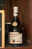 Restaurant. Old bottle of Bisquit cognac in the window. Bordeaux city, Aquitaine, Gironde, France