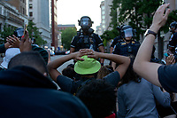 Demonstrators kneel before police officers during a protest in Washington, D.C., U.S., on Sunday, May 31, 2020, following the death of an unarmed black man at the hands of Minnesota police on May 25, 2020.  Credit: Stefani Reynolds / CNP/AdMedia