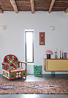 The living room has a modern, yet rustic feel with a beamed ceiling and tadelakt plaster flooring. A colourful African chair embroidered with pearls and a retro style sideboard are either side of the narrow window. A multi-coloured rag rug completes the picture.