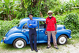 "JAMAICA, Port Antonio. Joseph ""Powder"" Bennett and Derrick ""Johnny"" Henry of the Mento band, The Jolly Boys standing in front of a vintage blue car."