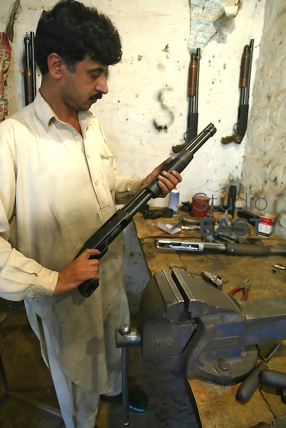 A gunsmith displays a home made shotgun in his workshop in Pakistan's most prominent arms producing village of Darra Adam Khel, Pakistan, Thursday, October 19, 2006. Darra is a dusty, Wild West-type town, crawling with intelligence agencies, drug smugglers and gun-toting Pathan tribesmen. Darra-built Kalashnikovs, not known for their durability, sell for US$30 to US$45 alongside knuckledusters, shotguns with telescopic sights and twelve bores made to look like M16 assault rifles. Much of the weaponry is made from scrap metal from shipyards. Pakistan's government's attempts to regulate the Darra weapon industry always ended in failure. Photo by Simon Lim/Pictobank.