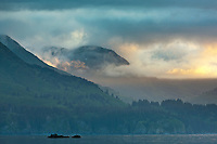 Clouds roll over a mountain along the shores of Kodiak Island, Alaska.