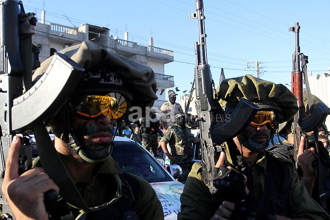 Palestinian militants from the Al-Nasser Brigades, an armed wing of the Popular Resistance Committees (PRC), hold their weapons during a rally in Rafah in the southern Gaza Strip on September 26, 2016, to mark the 17th anniversary of the creation of their group. Photo by Abed Rahim Khatib