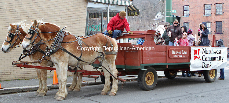 Winsted, CT-120713MK20 Rick Bunnell, from Bunnell Farm in Litchfield, looks back as revelers board the horse drawn wagon during Main Street Christmas festivities in Winsted on Saturday afternoon. Over a hundred locals toured the sidewalk along Main Street to enjoy horse-drawn hay rides, the roasting of marshmallows with local firefighters, pictures with Santa and the Christmas Tree lighting at East End Park. The event will also included hot chocolate, popcorn, cookies, carol singing, crafts and storytelling. Tricia Twomey, director of the parks and recreation department, said that this was the fifth year for the festival sponsored by Friends of Main Street and was supported by various local businesses.