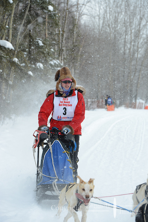 Arleigh Reynolds passes by University Lake during the first day of the World Championship Sled Dog Races, a highlight of the 2013 Anchorage, Alaska, Fur Rendezvous.