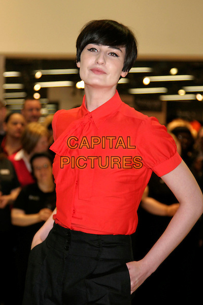 ERIN O'CONNOR.Opens the new M&S store at Colliers Wood, South London, England..May 1st, 2008.M & S Marks & Spencer half length red blouse tie hand in pocket .CAP/DS.©Dudley Smith/Capital Pictures
