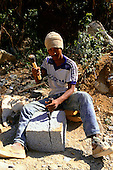 Brazil. Quarry worker using hammer and wedges to split a block of granite.