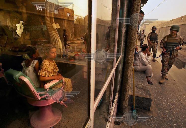 Girls sit in a beauty salon as soldiers patrol in the the Haifa Street section of Baghdad. This area is one of the most violent in the city; many US troops are prohibited from entering.