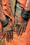 Kasanga, Zambia; wrinkled old woman's hands wearing wooden bangles on a ragged orange printed cloth wrap.